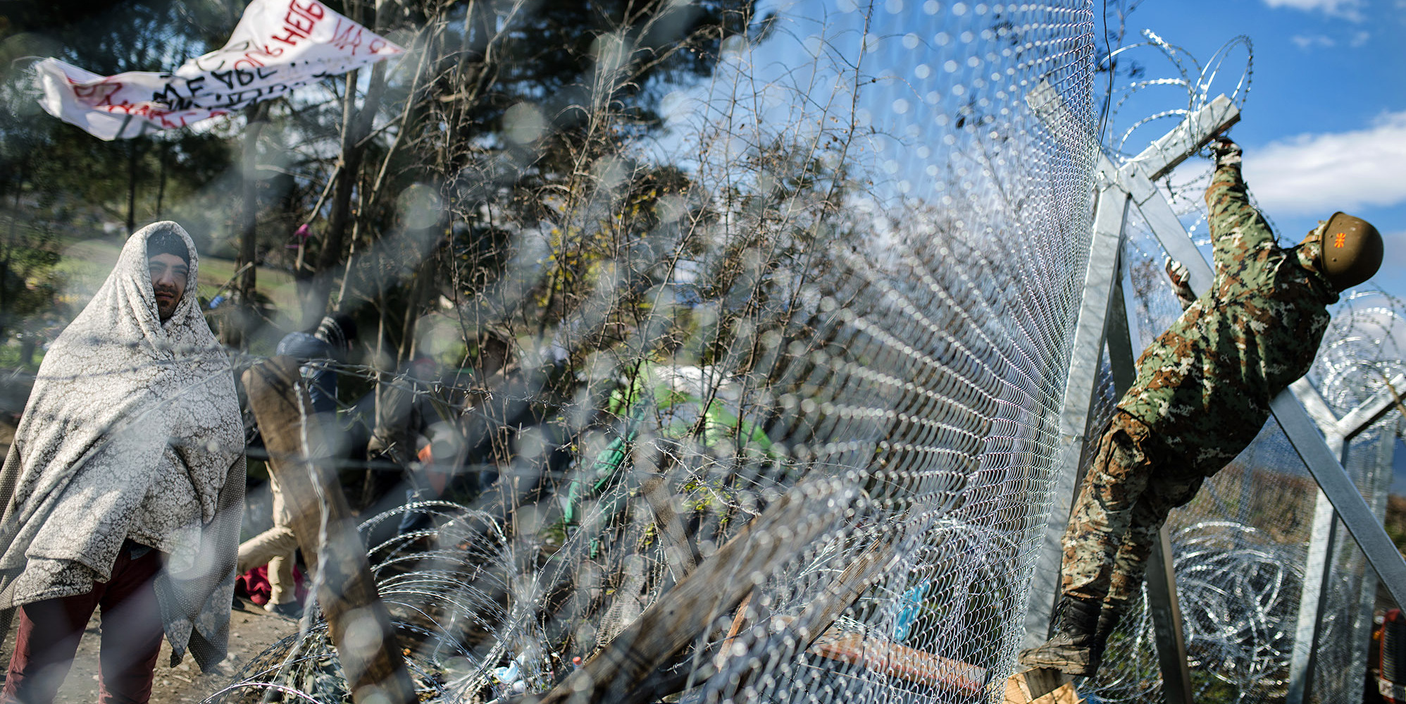 A migrant demonstrate looks on from behind a fence as he wait to cross the Greek-Macedonian border near Gevgelija on November 29, 2015.A group of migrants trying to enter Macedonia pelted the police with stones on November 28, injuring several officers as the small Balkan country became the latest to build a border fence aimed at checking the flow of newcomers. AFP PHOTO / ROBERT ATANASOVSKI / AFP / ROBERT ATANASOVSKI