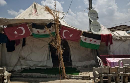 I rifugiati esprimono la loro gratitudine verso il paese che li ospita esponendo la bandiera turca a fianco a quella della Siria libera. Campo profughi di Boyunyogun, Altinozu. Turchia