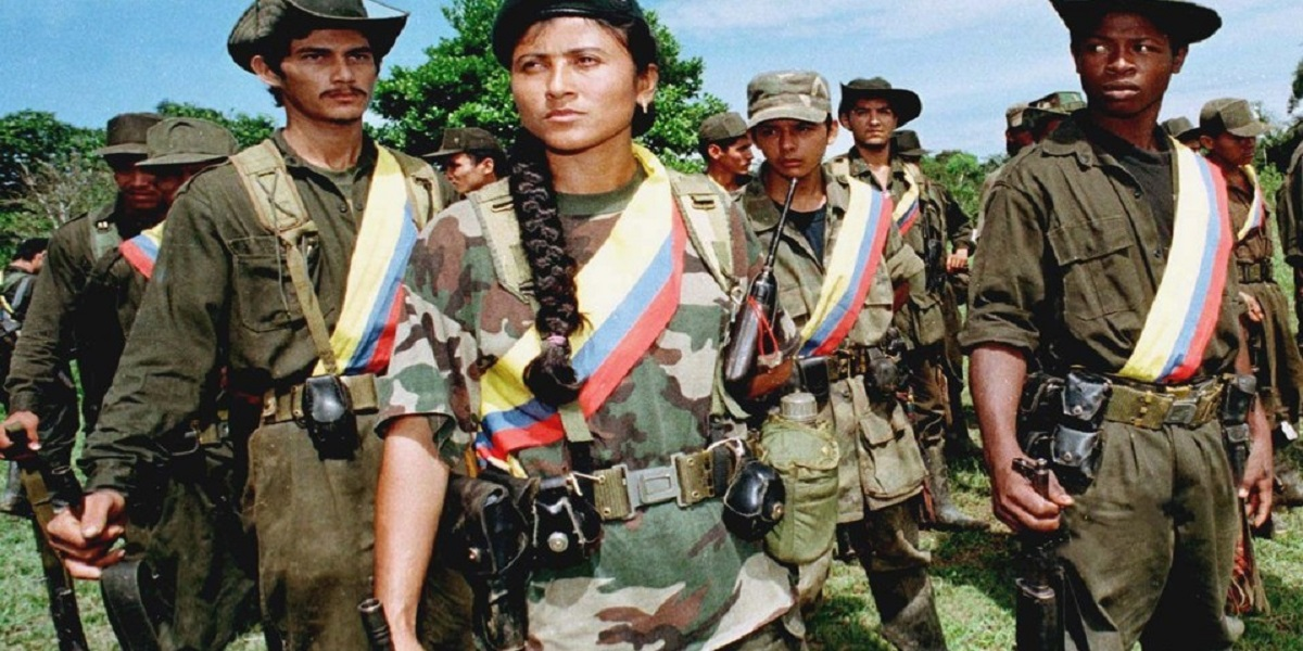 A woman guerrilla  stands to attention with her comrades-in-arms from the Fourth Front of the Revolutionary Armed Forces of Colombia (FARC), latin America's oldest and largest guerrilla force, during a training session in the jungle near the town of Miraflores, 300 km southeast  of the capital. The FARC's Fourth Front took part in the devastating attack on an anti-drug base in Miraflores last week in which more than 40 security force members died and more than 100 were taken prisoner. The attack was one of the worst in a nationwide rebel offensive that began last Monday and raged through Wednesday, leaving more than 140 people dead across the country. Picture taken 7AUG98. - RTXI3S5