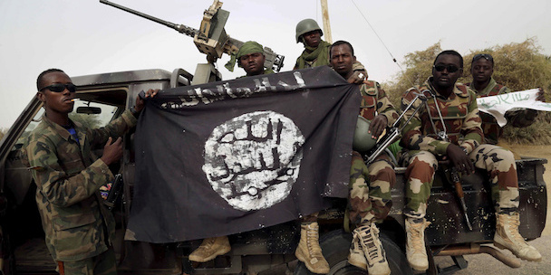 Nigerian soldiers hold up a Boko Haram flag 53