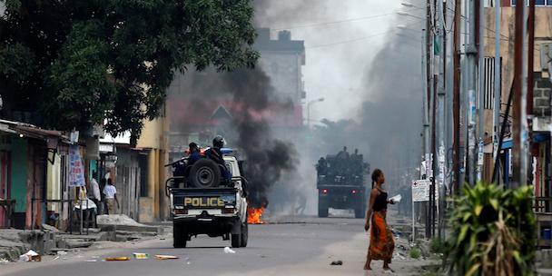Congolese policemen drive past a fire barricade