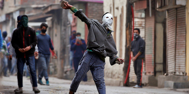 Kashmir. A demonstrator hurls a stone towards the Indian police