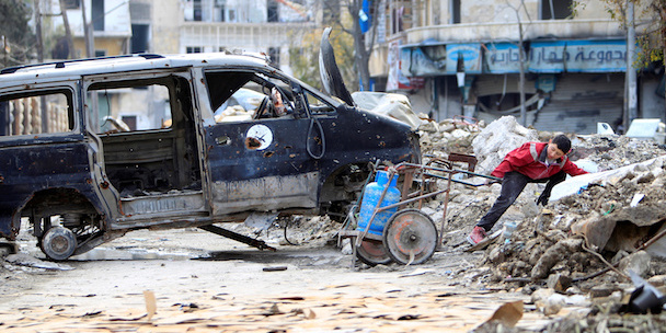 A boy pulls a gas bottle near rubble and a damaged vehicle in Aleppo