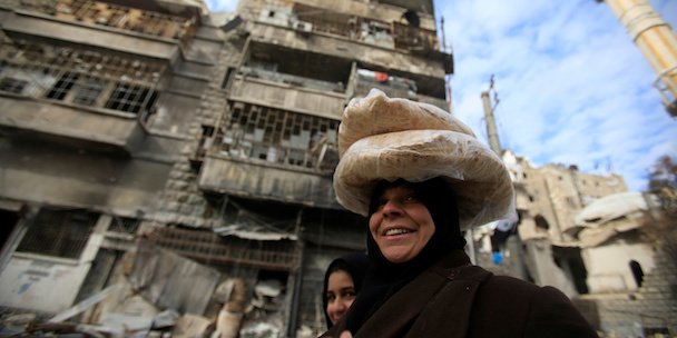 A woman carries bread on her head in Aleppo